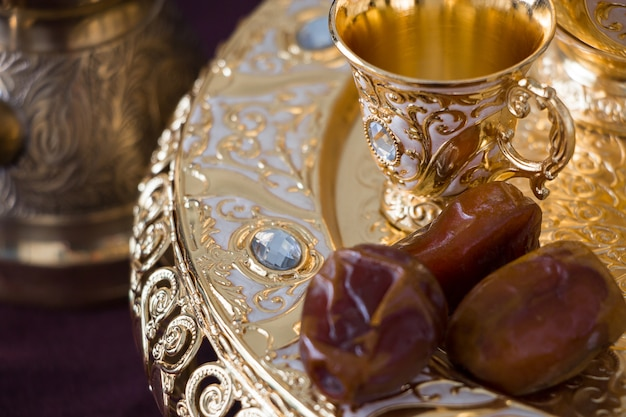Still life with traditional golden arabic coffee set with dallah