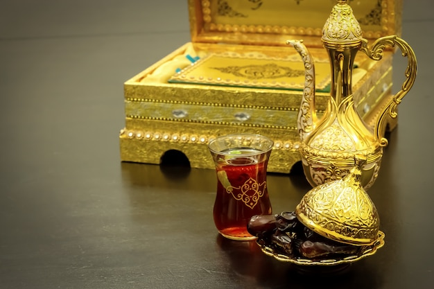 Still life with traditional luxury golden arabic coffee set with dallah, cup and dates. quran book. ramadan concept.