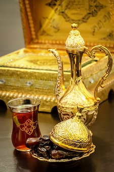 Still life with traditional luxury golden arabic coffee set with dallah, cup and dates. ramadan concept.