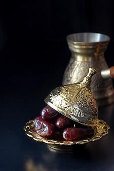 Jezva、カップ、日付が設定された伝統的な高級金色のアラビアコーヒーのある静物。ラマダンのコンセプトです。