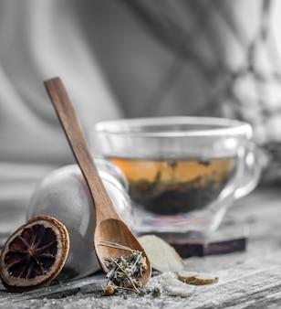 木製の背景に生姜とお茶の透明で香りの良いカップのある静物