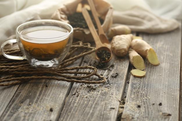 Натюрморт с прозрачной чашкой чая на деревянный стол