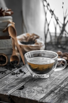 Still life with transparent cup of tea on wooden background