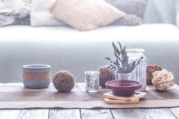 Natura morta con vari dettagli di un interno accogliente, sullo sfondo di un divano con cuscini, il concetto di comfort domestico