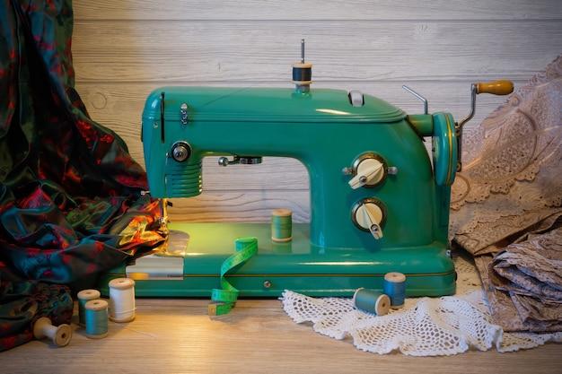 Натюрморт со старинной электрической швейной машиной, тканями и катушками с нитками