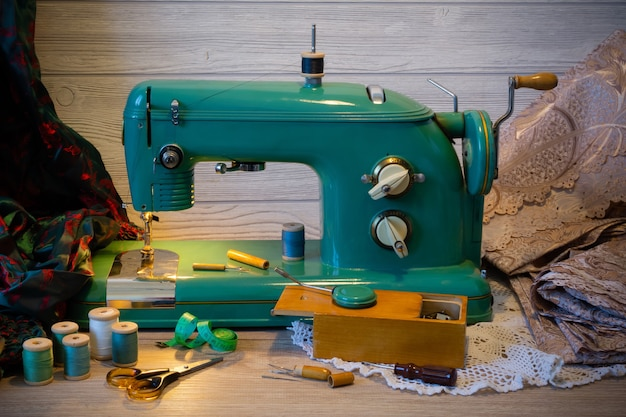 Still life with vintage electric sewing machine and a variety of sewing accessories