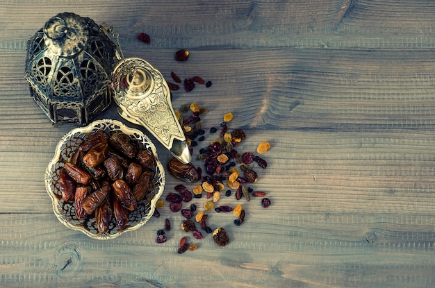 Still life with vintage orintal latern, raisins and dates on wooden background. retro style toned picture