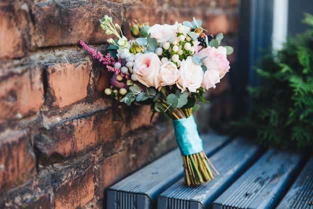 Still life with wedding bouquete stands on wooden surface near brick wall