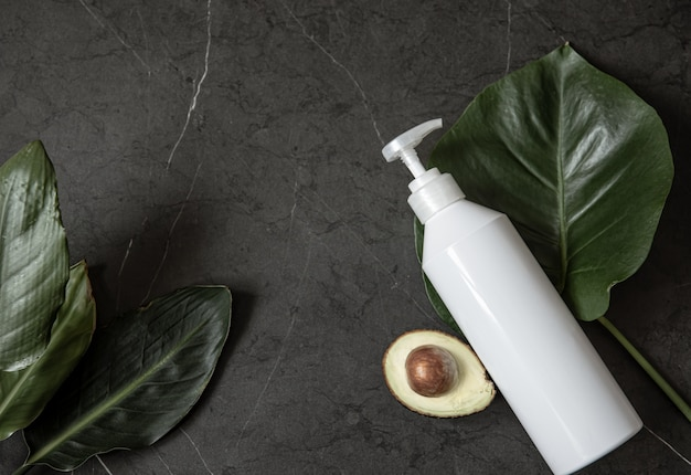 Still life with white cosmetic dispenser bottle mockup with avocado and leaves top view. beauty and hygiene concept.