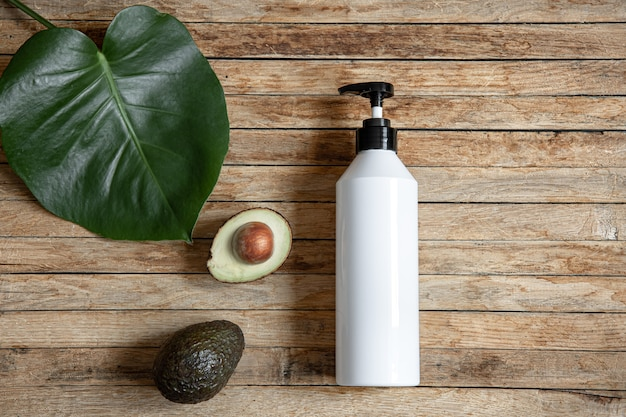 Still life with white mock-up bottle with dispenser and avocado. organic cosmetics and beauty concept.