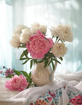 Still life with white and pink peonies in a white vase