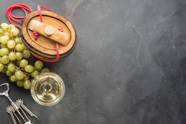 The still life with white wine, glass and old barrel
