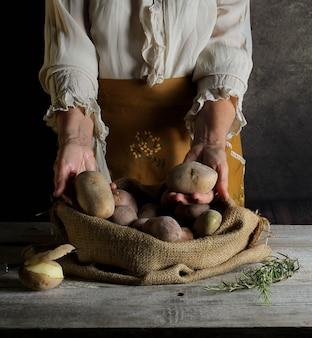 삼베 자루 내부에서 감자를 보여주는 여자와 정물화