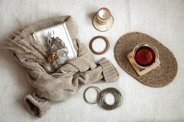 Still life with women's bracelets, a cup of tea on a wicker stand, a candle and a warm sweater, autumn comfort concept top view