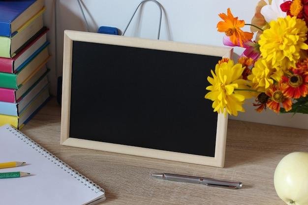 テーブルの上の黒い空白の背景の黒板と木製のフレームのある静物学校のモックアップ学校に戻る9月1日知識の日教師の日