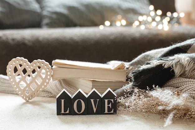 Натюрморт с деревянным словом любовь, книги и уютные предметы на размытом фоне с бокэ.