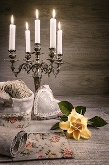 Still life with yellow rose, stuffed heart and vintage candlestick