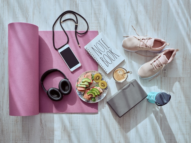 Still life on the wooden floor with a gym blind, healthy food, music helmets, coffee, pink shoes, thermos, note book and necklace