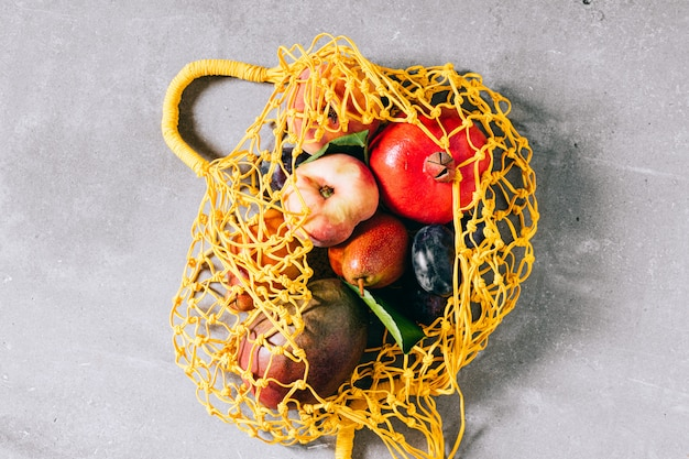 Still life of yellow biodegradable shopping bag with raw fruit