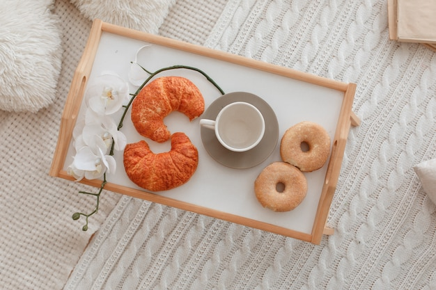 Stilllife of empty cup, croissants, donuts, tender orchid flowers on wooden tray.