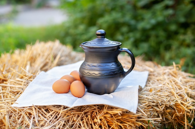 Stilllife in rustic style wirh clay jug, eggs on straw and burlap on straw in garden. milk in clay jug. organic product.