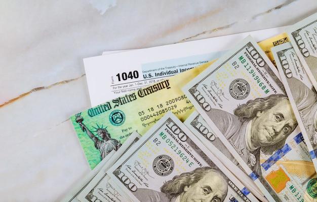 Stimulus economic tax return check and us 100 dollar bills currency