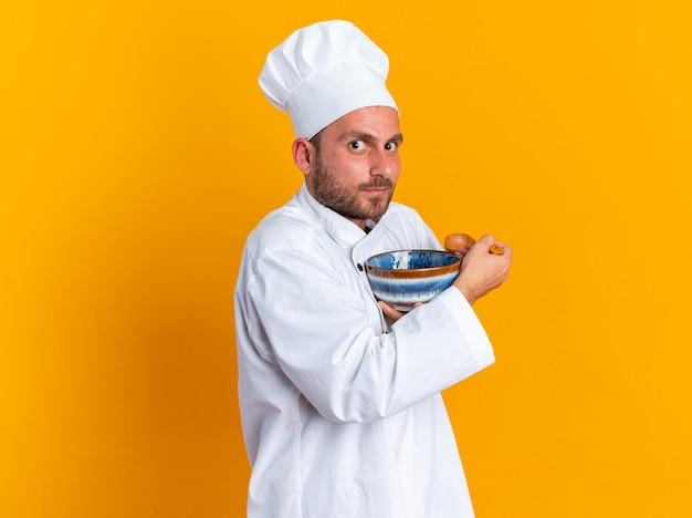 Stingy young caucasian male cook in chef uniform and cap standing in profile view looking at camera holding bowl and spoon hugging bowl isolated on orange wall with copy space