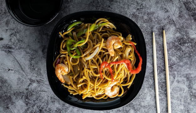 Stir cold noodles with vegetables and shrimp in a black bowl. chalkboard space. top view.