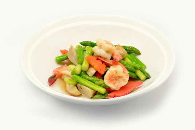Stir fried asparagus with shrimp on white plate and white background.