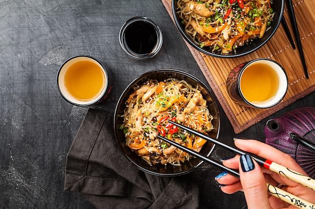 暗い背景、上面図の上にプレートで鶏肉と野菜と中華鍋麺で炒めた