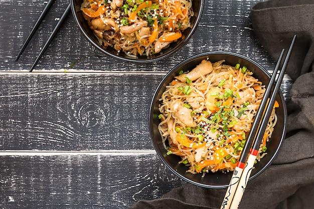 어두운 표면, 평면도 위에 접시에 닭고기와 야채와 함께 냄비 국수에 볶음