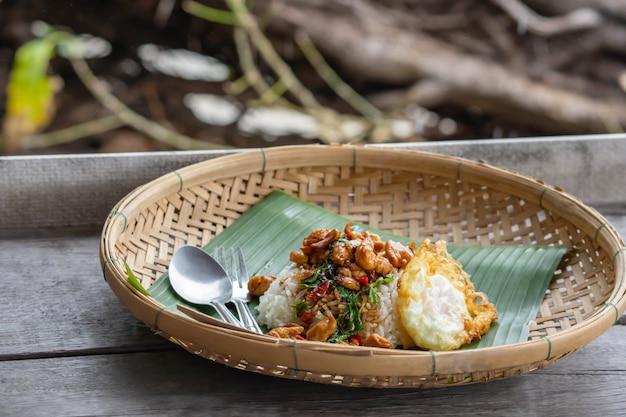 フライドバジルリーフチキンライスと木製のテーブルの竹かごに目玉焼きを入れます。