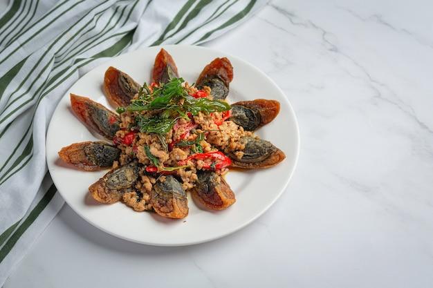 Basilico saltato in padella con uovo piccante del secolo servito con riso al vapore e salsa di pesce al peperoncino, cibo tailandese.