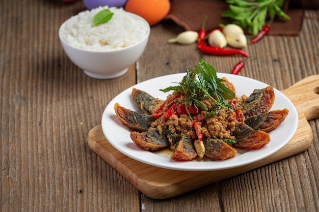 Stir fried basil with spicy century egg served with steamed rice and chili fish sauce, thai food.
