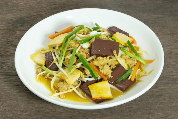 白いセラミックプレートで揚げ豆もやしをかき混ぜます。もやしの炒め物に黄色い豆腐、ひき肉、にんじん、豚の血、エシャロットを入れて炒めます。タイ料理。