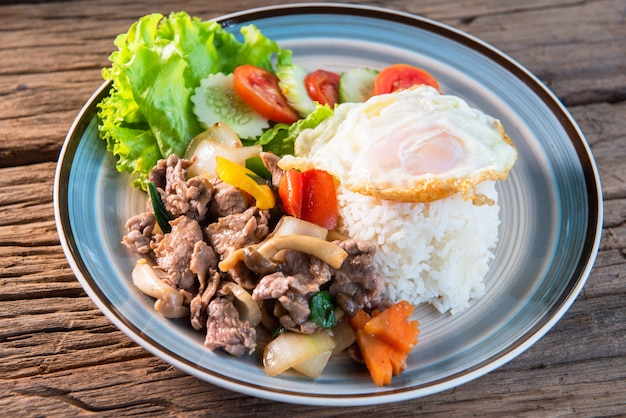 Stir fried beef with mushrooms, green peppers and onions topped with rice, fried eggs