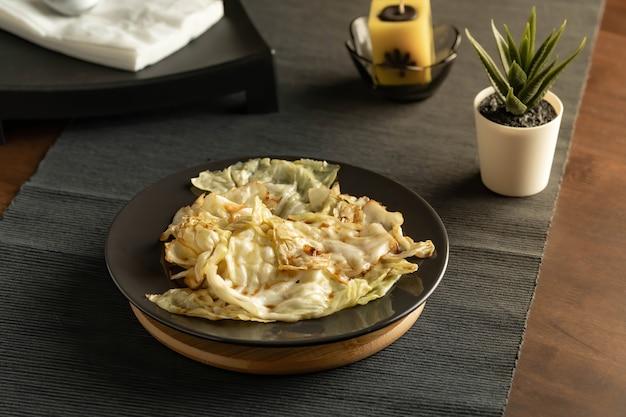 Перемешать жареную капусту с рыбным соусом, подаваемую в черном блюде