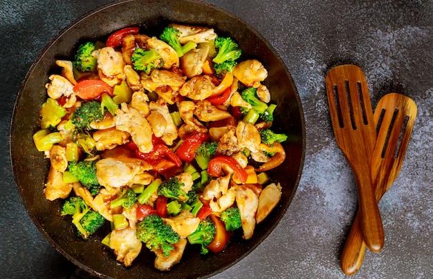 Stir-fried chicken with broccoli, bell pepper on dark surface