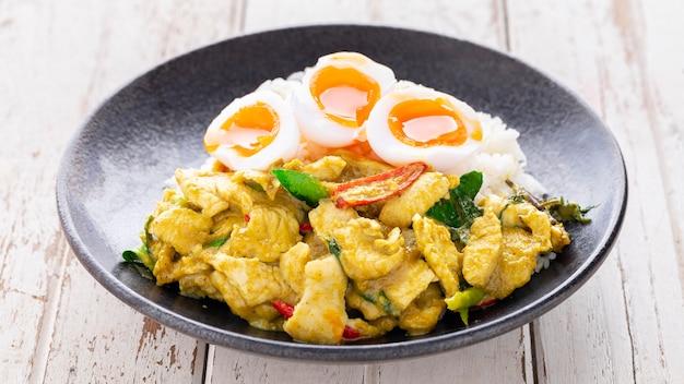 Жареная курица с зеленой пастой карри, вареным рисом и жидким желтком в черной керамической тарелке на белом фоне текстуры старого дерева, пуд кео ван гай, тайская кухня