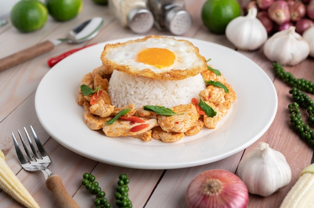 Stir fried chili paste chicken with rice fried eggs in white plate on wooden table.