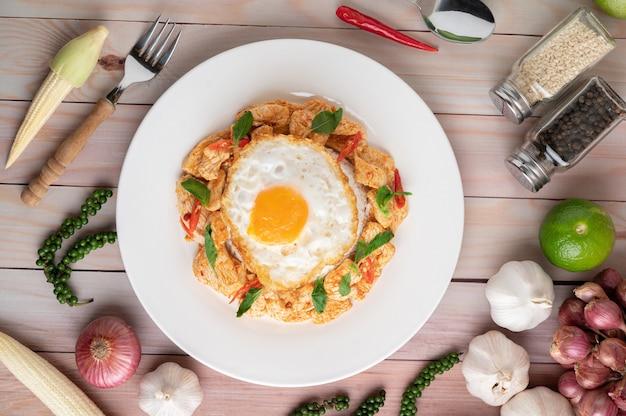 Stir fried chili paste pollo con riso uova fritte nel piatto bianco sulla tavola di legno.