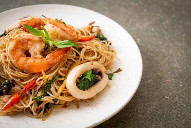 Stir-fried chinese noodle with basil, chilli, shrimps and squid - asian food style