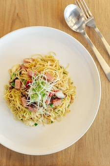 Stir fried chinese noodle with ham and crab meat on wooden table background