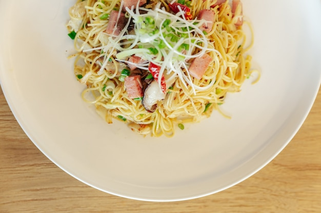 Stir fried chinese noodle with ham and crab meat on wooden table background.