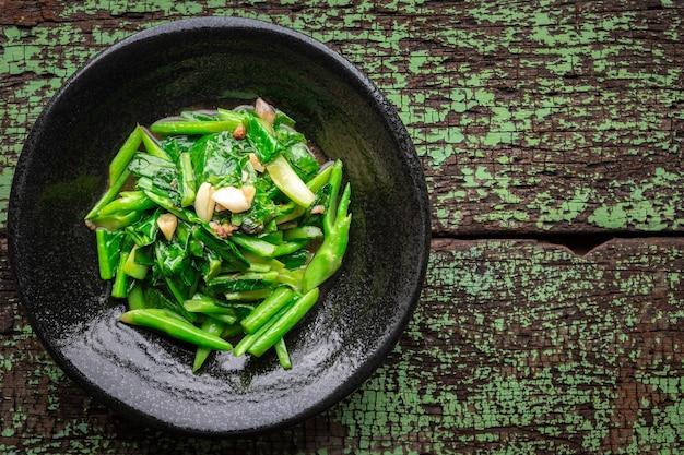 텍스트, 위쪽 보기, 콜라드 그린을 위한 복사 공간이 있는 녹색 오래된 나무 질감 배경의 검은 세라믹 접시에 소금에 절인 생선과 마늘을 넣은 튀긴 콜라드