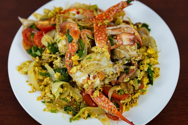 Stir fried crab with curry powder, closeup, thai food on a wooden background