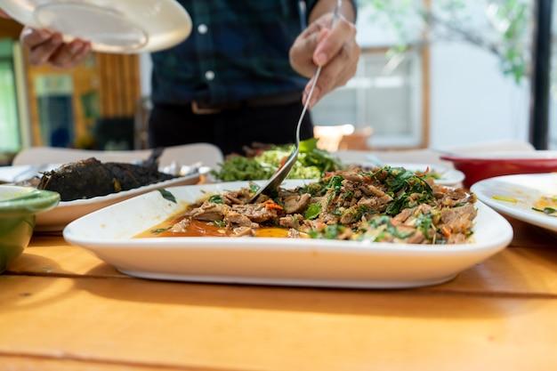 木のテーブルの上の正方形の白い皿にバジルと一緒に揚げた鴨をかき混ぜ、昼食のために彼の大きなスプーンでアジア人によってすくわれます。