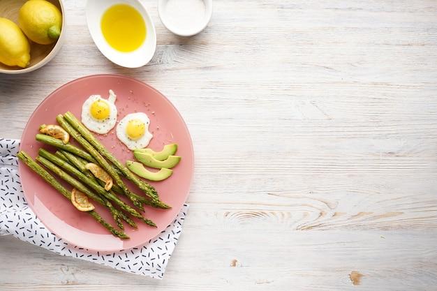 Жареные яйца с зеленой спаржей в тарелке на деревянном фоне, место для текста. плоская планировка.