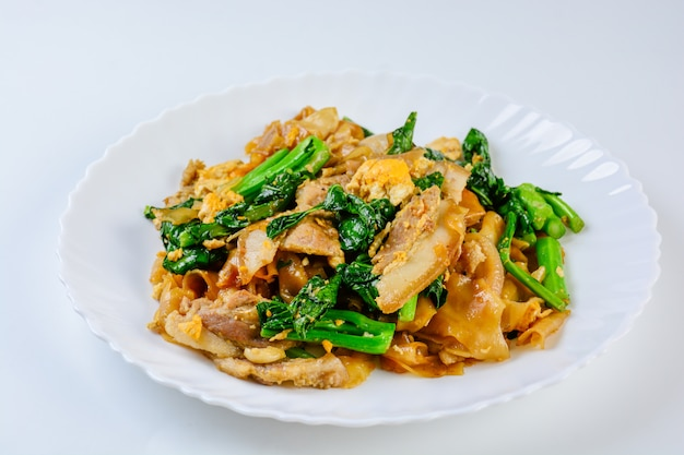 Stir-fried fresh rice-flour noodles with sliced pork, egg and kale. quick noodle stir-fry.
