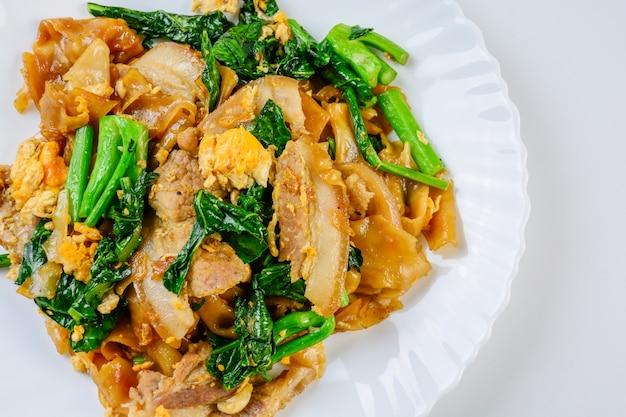 Stir fried fresh rice flour noodles with sliced pork, egg and kale, quick noodle stir fry,